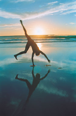 A photo of a person doing a handstand on the beach.  NLP training is transformational for yourself and for those you coach.